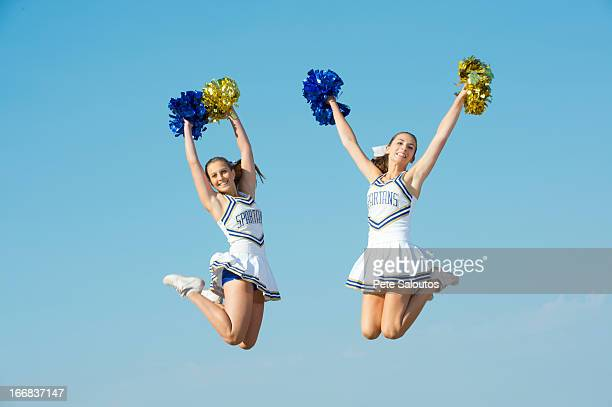 Caucasian cheerleaders jumping in mid-air