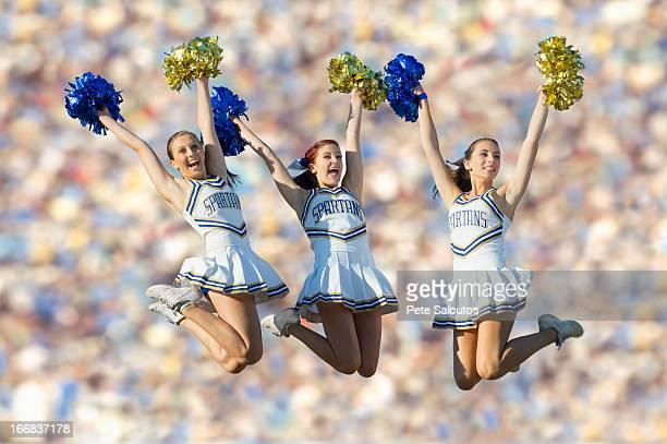 Caucasian cheerleaders jumping in mid-air