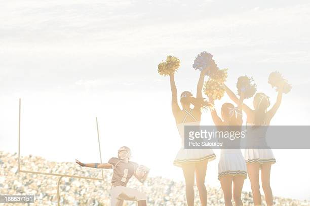 caucasian cheerleaders on sidelines at football game - high school football stock pictures, royalty-free photos & images