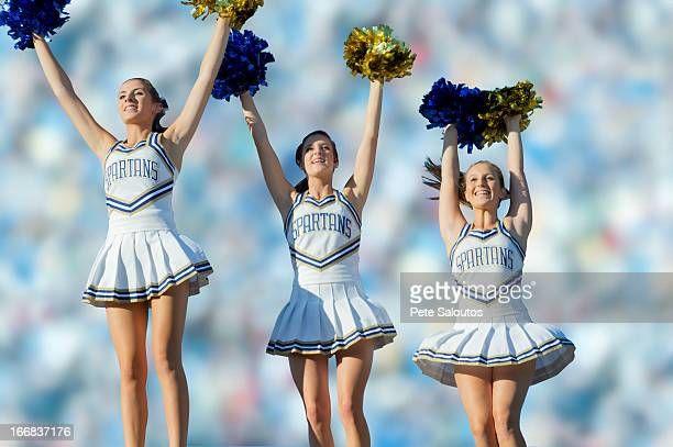 Caucasian cheerleaders on sidelines at football game
