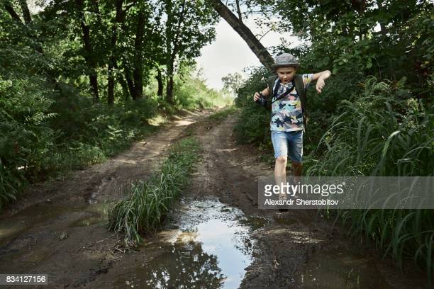 Caucasian child jumping over a puddle