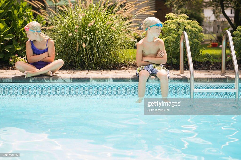 Caucasian children arguing at swimming pool : Foto stock