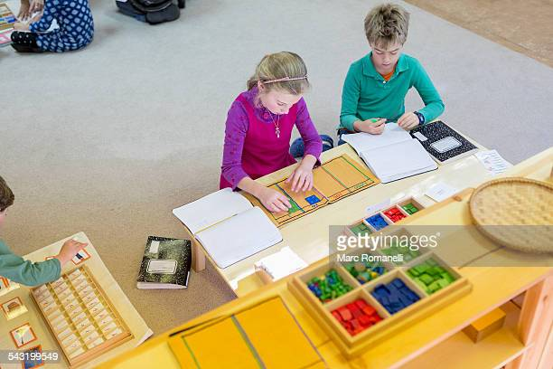 caucasian children at table in classroom - montessori education stock pictures, royalty-free photos & images