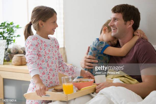 Caucasian children bringing father breakfast in bed
