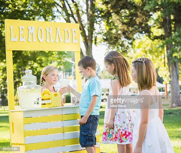 Caucasian children buying drinks at lemonade stand
