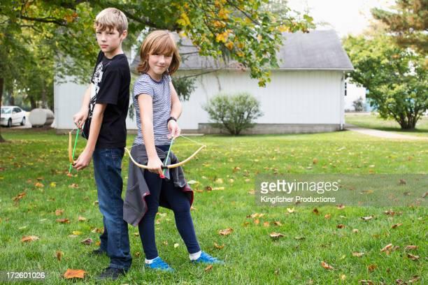 caucasian children drawing bows and arrows - arco y flecha fotografías e imágenes de stock