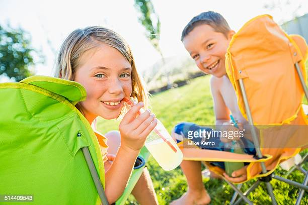 Caucasian children drinking soda in backyard