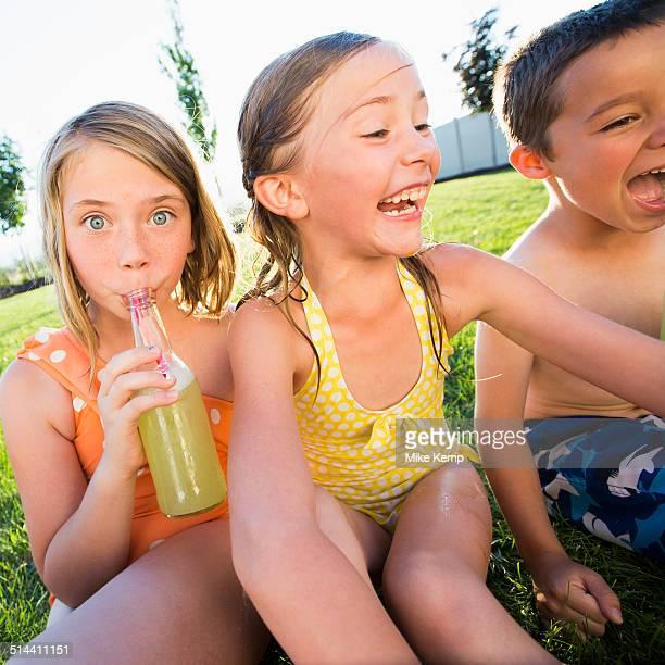 Caucasian children drinking soda in backyard