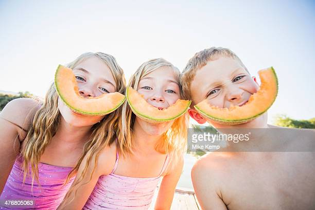 Caucasian children eating cantaloupe slices