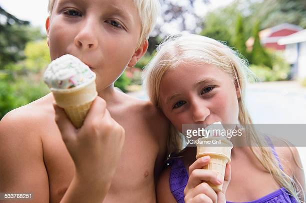 Caucasian children eating ice cream near swimming pool
