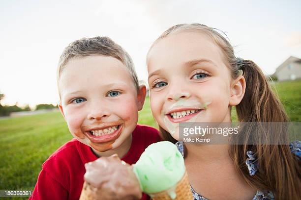 caucasian children eating ice cream outdoors - girl sitting on boys face stock photos and pictures