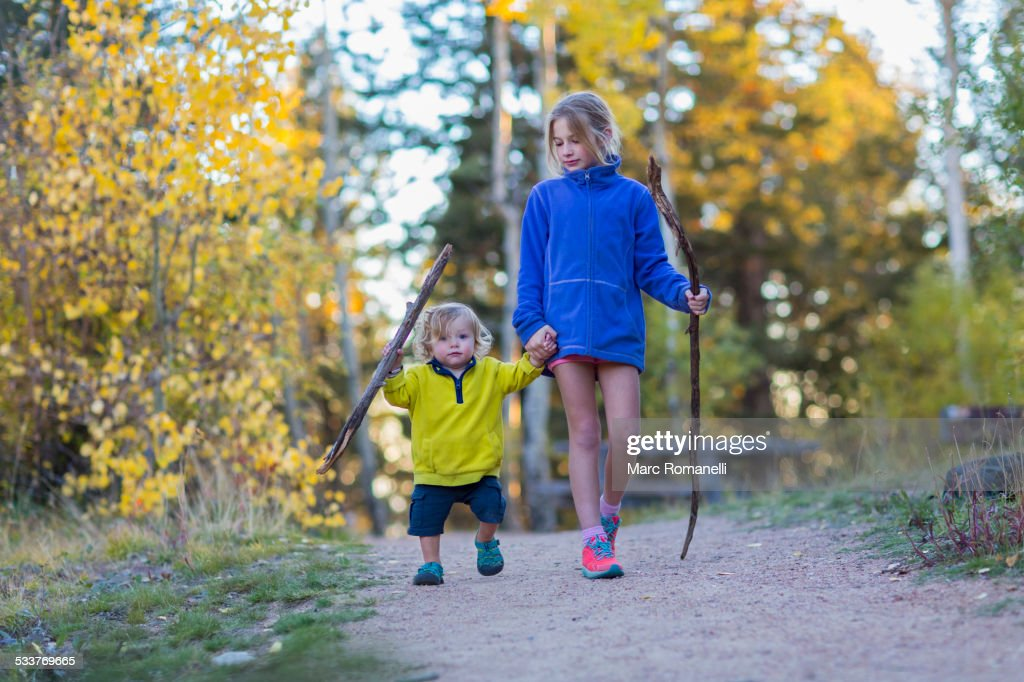 Caucasian children hiking on dirt path in forest : Foto stock