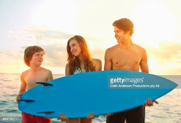 Caucasian children holding surfboard on beach