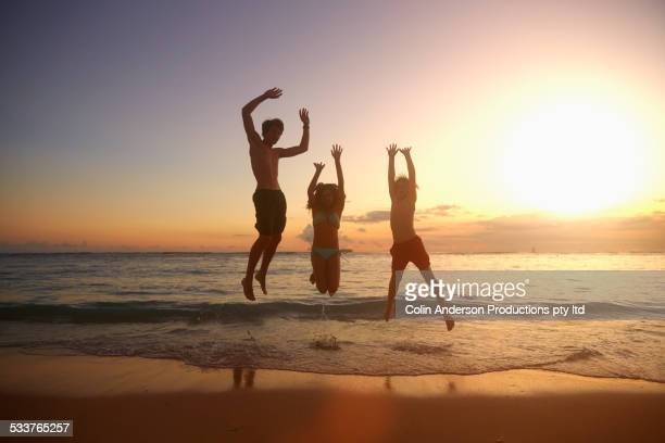 Caucasian children jumping for joy on beach