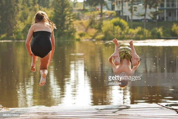 Caucasian children jumping into lake