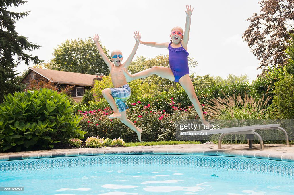 Caucasian children jumping into swimming pool : Foto stock