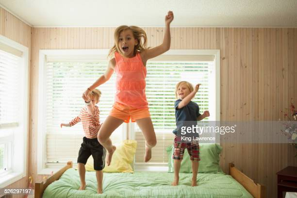 Caucasian children jumping on bed