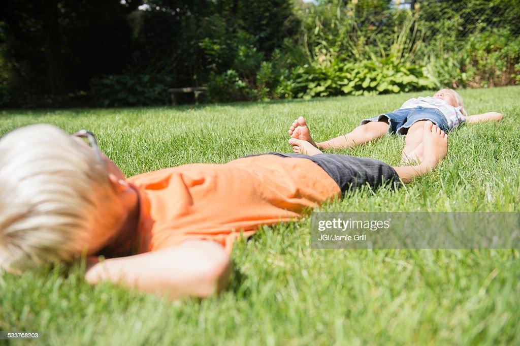 Caucasian children laying on lawn in backyard : Foto stock