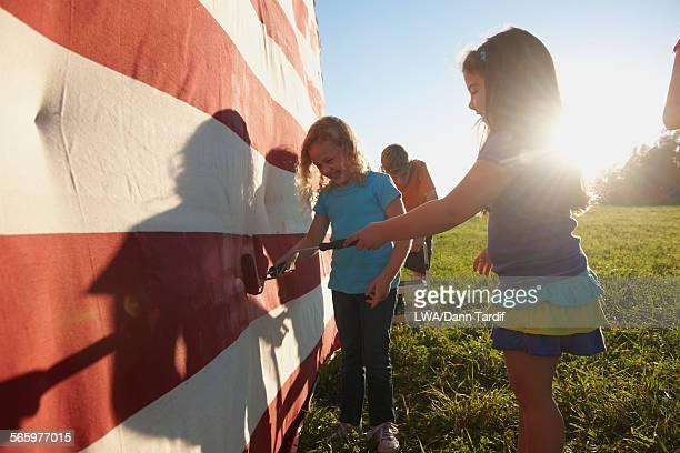 Caucasian children painting American flag in field
