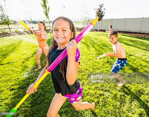 Caucasian children playing in sprinkler in backyard