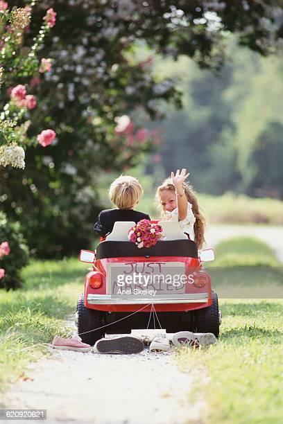 Caucasian children playing newlyweds outdoors
