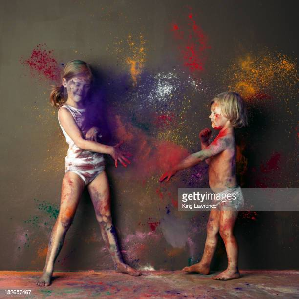 Caucasian children playing with paint