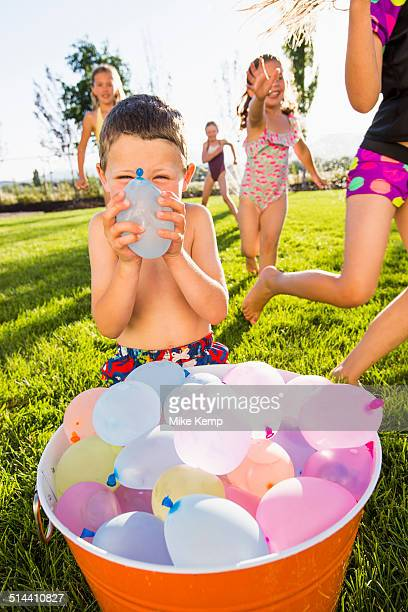 Caucasian children playing with water balloons in backyard