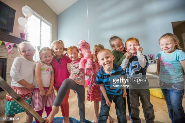 Caucasian children posing with pinata at party