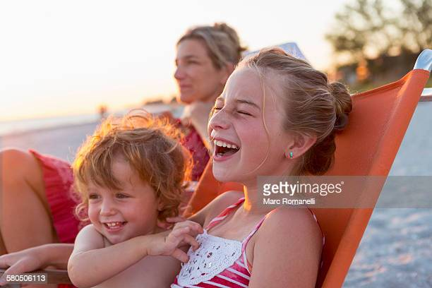 Caucasian children relaxing in lawn chair on beach