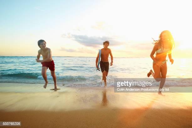 Caucasian children running from ocean on beach