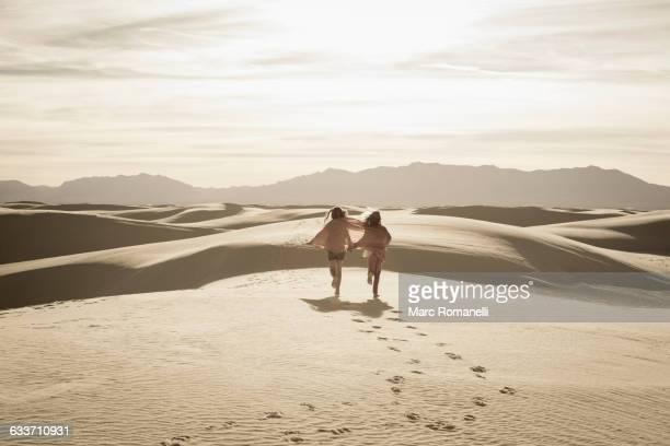 Caucasian children running in desert