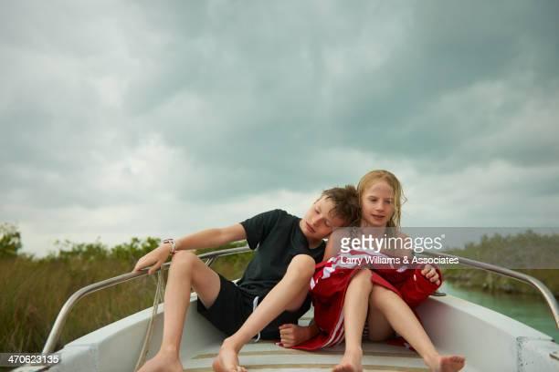 caucasian children sitting on boat - knaben in badehosen stock-fotos und bilder