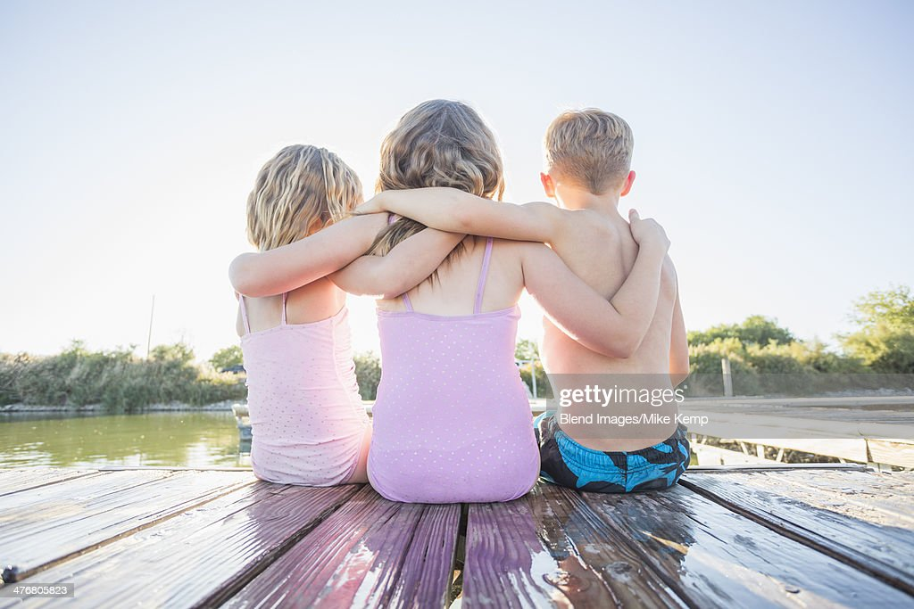 Caucasian children sitting on dock : Stock Photo