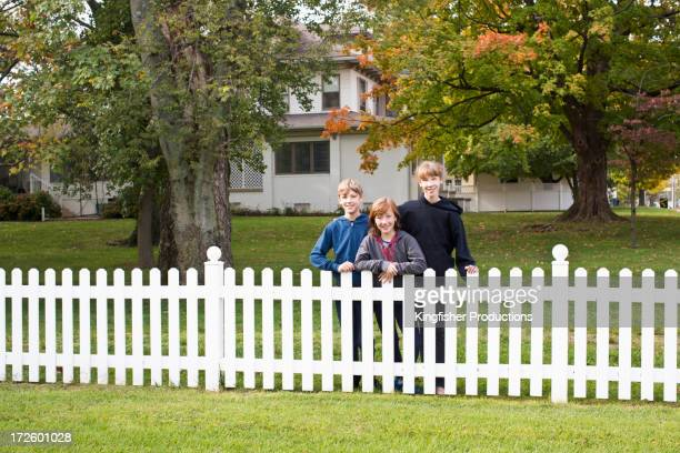 Caucasian children smiling by house