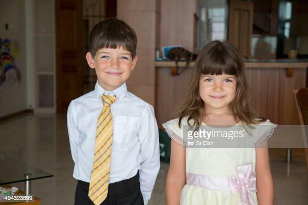 Caucasian children smiling in formal wear