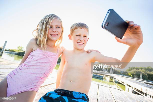 Caucasian children taking selfie with cell phone