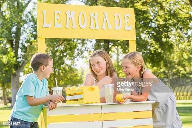 Caucasian children talking at lemonade stand
