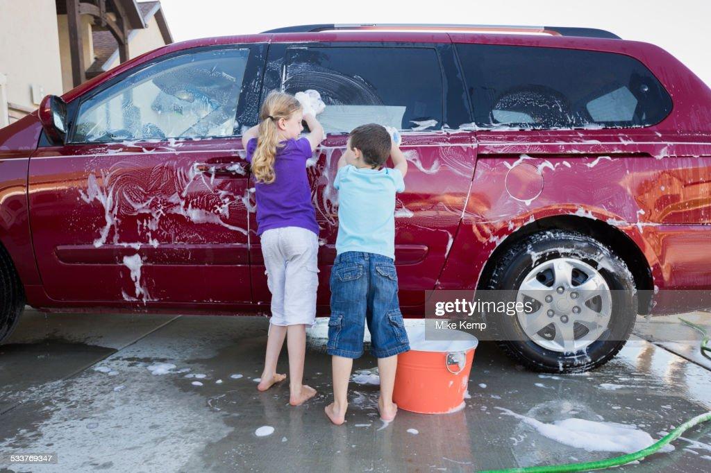 Caucasian children washing car in driveway : Foto stock