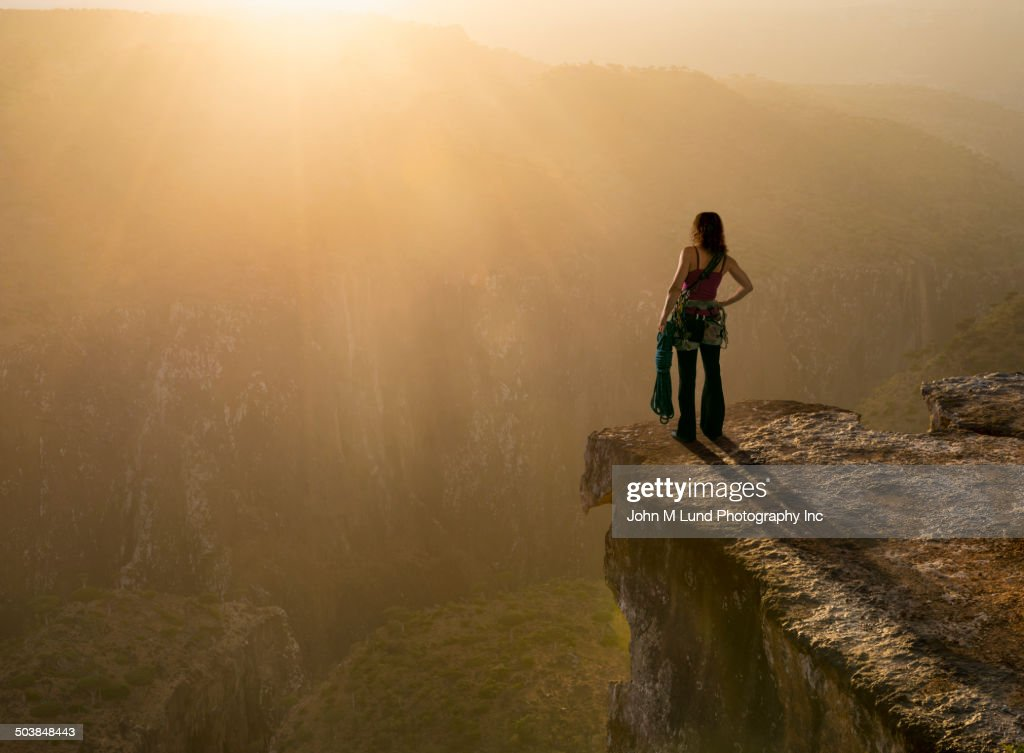 Caucasian climber overlooking rocky mountaintop : Stock Photo