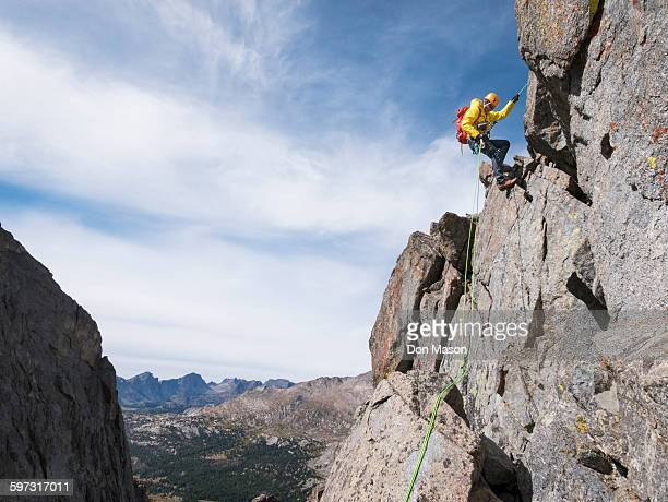 Caucasian climber rappelling on mountainside