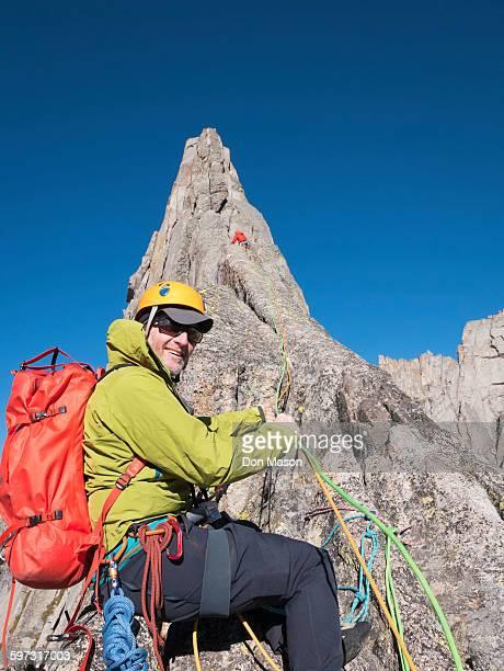 Caucasian climber smiling on mountainside