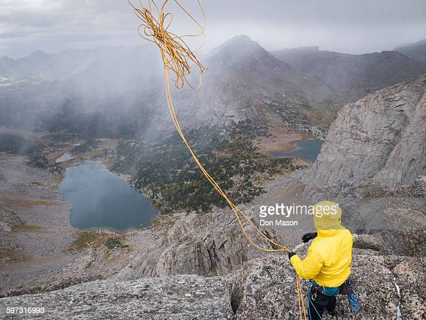 Caucasian climber throwing rope down mountainside