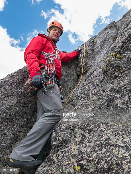 Caucasian climber using rope on rock