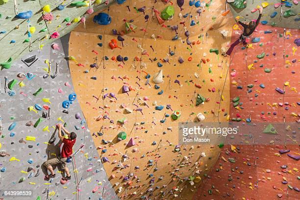 caucasian climbers scaling rock wall - クライミングウォール ストックフォトと画像