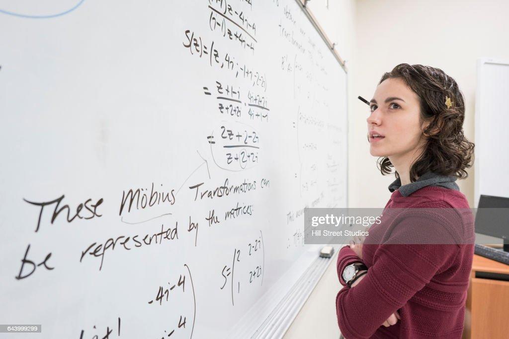 Caucasian college student reading whiteboard : Stock Photo