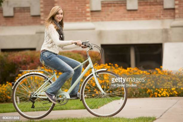 caucasian college student riding bicycle on campus - caldwell idaho stock pictures, royalty-free photos & images