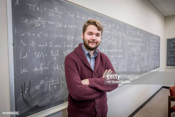 caucasian college student standing at chalkboard - mathematician stock pictures, royalty-free photos & images