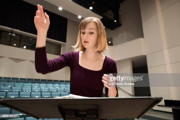 Caucasian conductor gesturing at podium