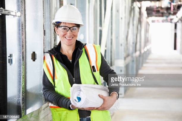 Caucasian construction worker carrying blueprints