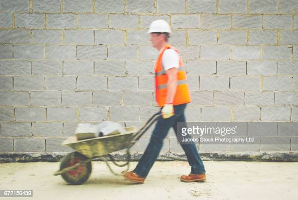 Caucasian construction worker carrying concrete in wheelbarrow